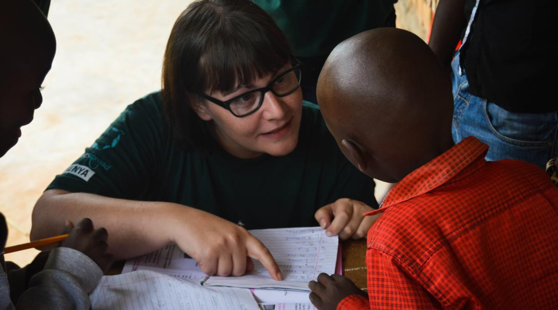A Projects Abroad teaching volunteer helps children in Kenya with their school lesson.